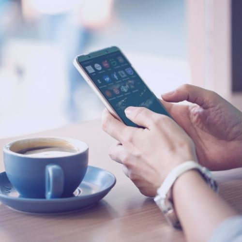 Customer using loyalty apps on mobile phone with coffee